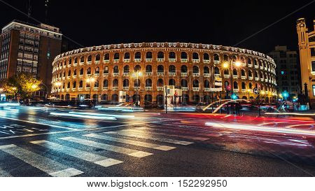 Night view of a Bullring Arena in Valencia Spain. Car traffic lighting trail motion blurred people. Dark sky.