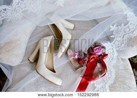 Beautiful bouquet shoes and perfume bottle for bride and groom. Beauty of wedding accessories indoors. Close-up bridal bunch of florets and perfumery. Female decoration. Colorful flowers for woman