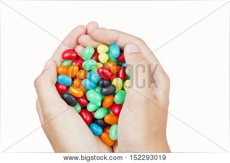 two hands holding many brightly colored jelly beans on a white background