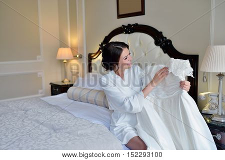 Beautiful bride in robe is watching a wedding dress. Beauty model girl in white clothes. Female portrait with bridal gown for marriage. Woman with curly hair and lace veil. Cute lady indoors
