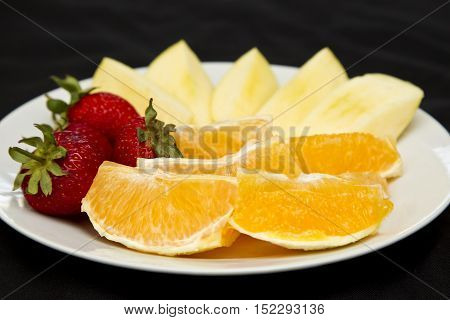Plate of fruit to be eaten for breakfast isolated on a black background