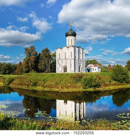 Church Intercession on Nerl River 12th century Golden Ring tour Bogolyubovo Vladimir Russia. Panoramic view with reflection and cloudy sky