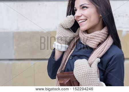 Pretty brunette woman in winter outfit using her phone