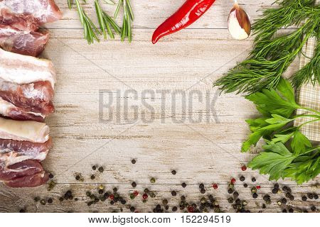 Fresh meat : raw pork meat with red chili pepper dill garlic and rosemary on wooden board