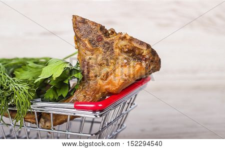Smoked pork ribs in a shopping cart with dill and parsley