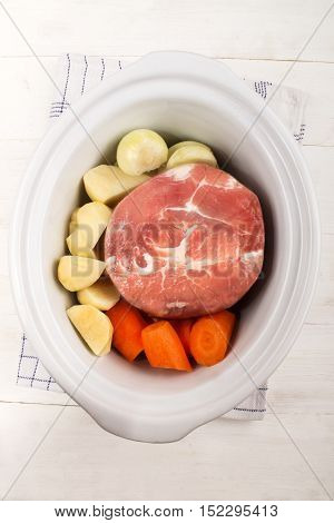 prepare a white slow cooker with ham carrot potato and onion on kitchen towel