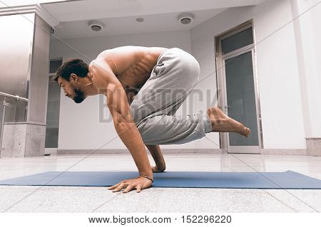Athletic Strong Man Practicing Difficult Yoga Pose.