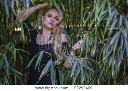 green, beautiful blonde with long black discharge between branches and trunks of vegetation