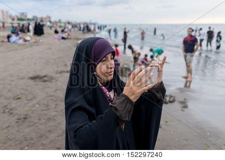Beautiful Muslim woman on the beach of Caspian sea in Iran