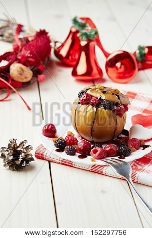Baked apple with berries and chocolate sauce. Wooden background. Healthy lifestyle.Diet and weight loss concept. Low calories dinner. Vitamin B. Healthy food.