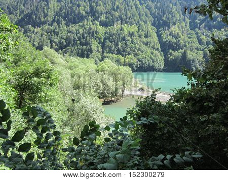 The lake formed in the gorge among the mountains covered with the wood