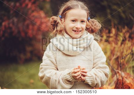 cute dreamy kid girl in warm knitted sweater and scarf playing in the garden in late autumn with dried hydrangea flowers