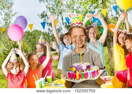 Happy young boy in party hat holding birthday cake, standing among his friends at the outdoor party