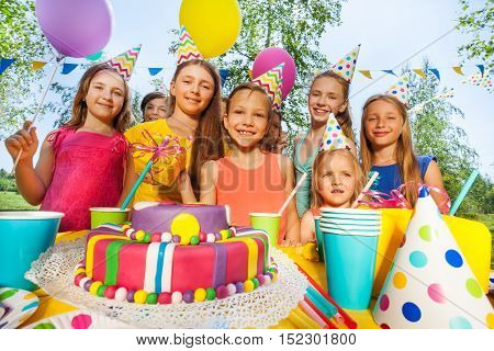 Group of adorable kids having fun at B-day party standing next to the birthday cake