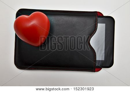 Closeup of tablet in leather case and cute little red heart