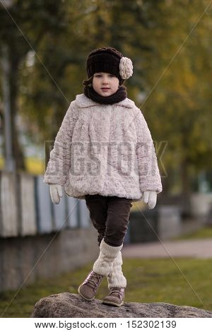 Little fashionable girl in warm clothes in the city