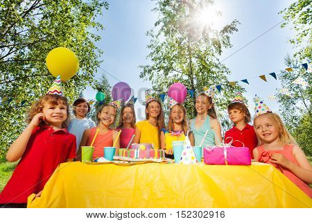 Big group of happy age-diverse kids standing in a row next to the birthday cake at the outdoor party
