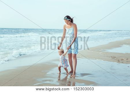 Daughter and mother at the sea. Daughter and mother at the sea. Mom teaches daughter to make first steps