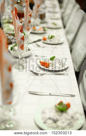 table with a white tablecloth for celebrations and dishes