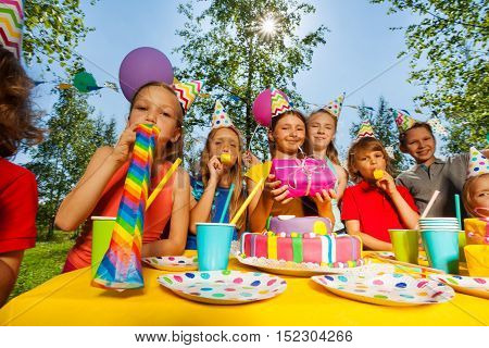 Big group of happy kids in party hats blowing whistles at outdoor birthday party