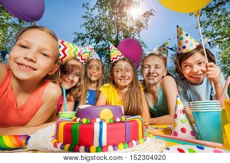 Six happy kids in party hats, standing in a row around birthday cake at the outdoor party