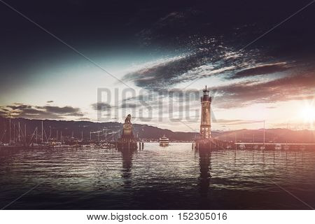 Sunset over Lindau harbor lighthouse and lion with an approaching ferry or tour ship and the glow of the sun reflected on the water, Bavaria, Germany