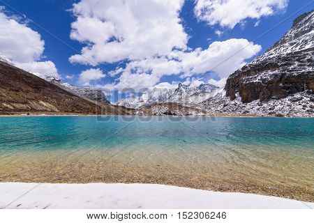 Milk lake on topgreen and blue with snow beach on the top of snow mountains with blue sky and clouds background at Yading Nature Reserve China.