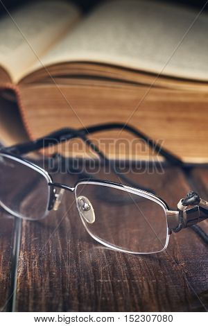 Reading glasses in front of old yellow book on rustic wooden background