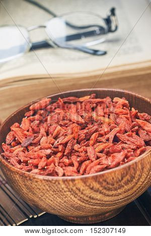 Dried goji berries in wooden bowl as a healthy snack