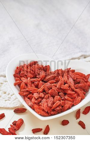 Dried goji berries in heart shaped ceramic bowl on white table. Copy space