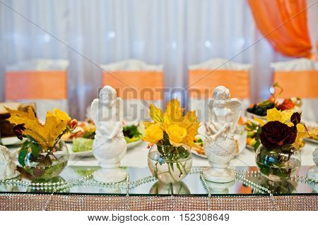 Yellow Autumn Leaves In Vases With Plaster Angels At The Wedding Table Newlyweds