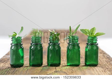 Green Bottle of essential oil with Fresh herbs and medicinal plants on wooden background.