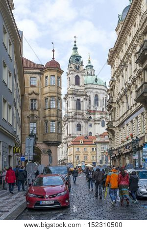 PRAGUE, OCTOBER 15: Mostecka Street with the Town Belfrey by St. Nicholas Church on October 15, 2016 in Prague, Czech Republic. Prague is full of beautiful historic buildings.