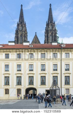 PRAGUE, OCTOBER 15: Tourists in front of a well  and Treasury on the Second Courtyard in Prague Castle with towers from St. Vitus in background  on October 15, 2016 in Prague, Czech Republic.