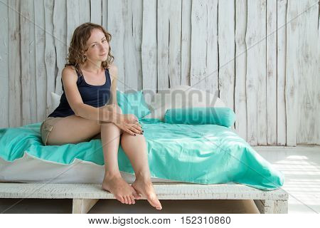 Happy young woman in bed, looking at the camera