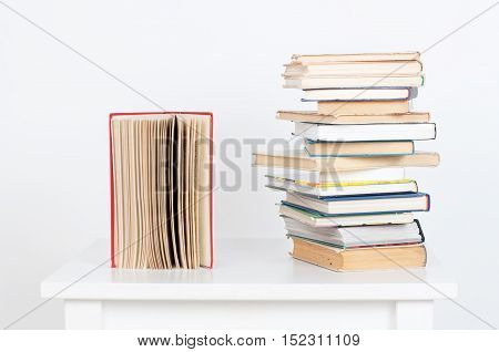 Stack of hardback books and old open book on white wall background. Search for relevant and necessary information in a large number of sources during studies or work.