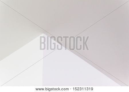 Construction details: Plastered board ceiling and wall corner with reflecting of fluorescent light