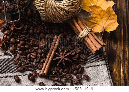 Autumn spices with coffee beans and maple leaves on wooden table. View from above.