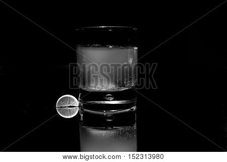 a glass with a medicine that dissolves to prevent influenza winter's bad, all reflection and black background