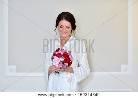 Beauty bride in dressing gown with bouquet indoors. Beautiful model girl in colorful wedding robe. Female portrait of cute lady. Woman with hairstyle