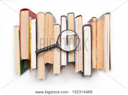 Stack of hardback books with magnifying glass isilated on white background, top view. Search for relevant and necessary information in a large number of sources during studies or work.