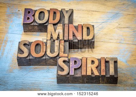 body, mind, soul and spirit word abstract -text in vintage letterpress  wood type printing blocks against grunge wood