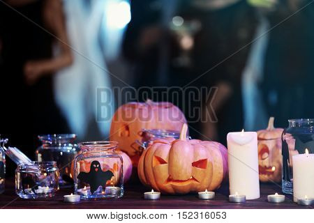 Glass jars, candles and Halloween decor on blurred background