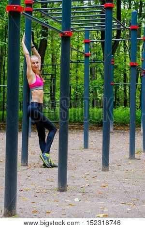 Young slim woman sports portrait on the training ground in a park