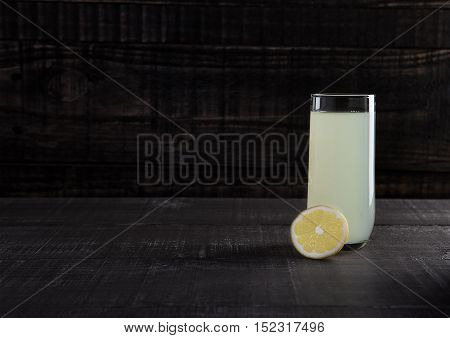 Glass of healthy lemon lemonade juice with fruit on wooden background