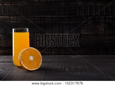 Glass of healthy orange juice with fruit on wooden background