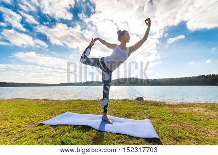 Young woman doing yoga near lake outdoors, meditation. Sport fitness and exercising in nature, autumn sunset