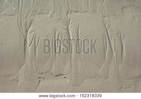 Water pattern on a sand after fall of tide painting an artificial picture structure at the coast line