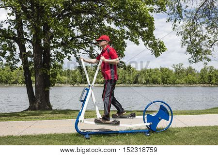 horizontal image of a man on an elliptical out door exercise machine situated next to a beautiful lake surrounded by trees.