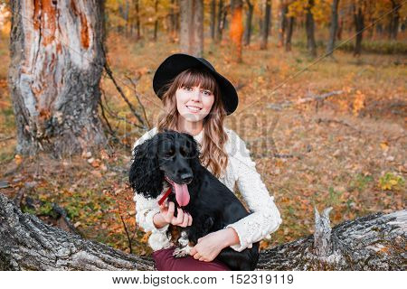 Young woman playing with black puppy in the autumn forest.